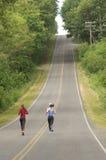 Zwei Frauen, die auf landwirtschaftliche Straße laufen lizenzfreies stockbild