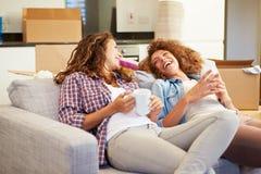 Zwei Frauen, die auf neuem Haus Sofa With Hot Drink Ins sich entspannen Lizenzfreie Stockfotografie