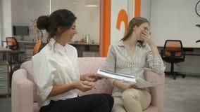 Zwei Frauen, die auf Sofa im Büro spricht und bespricht die emotional in Verbindung stehenden und lachenden Arbeitspläne, Büro si stock video footage