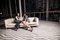 Zwei Frauen, die auf Sofa sitzen Lizenzfreie Stockfotografie