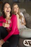 Zwei Frauen, die auf Sofa Watching Fernsehtrinkendem Wein sitzen Stockfoto