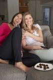 Zwei Frauen, die auf Sofa Watching Fernsehtrinkendem Wein sitzen Lizenzfreie Stockfotografie