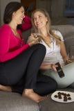 Zwei Frauen, die auf Sofa Watching Fernsehtrinkendem Wein sitzen Lizenzfreies Stockfoto