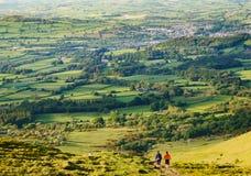 Zwei Frauen, die auf Spur mit Bauernhöfen und Landstadt in den Di gehen stockfoto