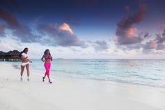 Zwei Frauen, die auf Strand laufen Lizenzfreies Stockbild