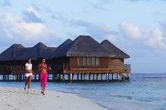 Zwei Frauen, die auf Strand laufen Lizenzfreie Stockfotos