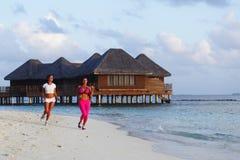 Zwei Frauen, die auf Strand laufen Lizenzfreies Stockfoto