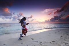 Zwei Frauen, die auf Strand laufen Stockbilder