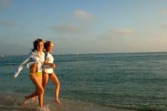 Zwei Frauen, die auf Strand laufen Stockbild