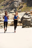 Zwei Frauen, die auf Strand laufen Lizenzfreie Stockbilder