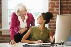 Zwei Frauen, die am Computer im zeitgenössischen Büro arbeiten Stockbilder
