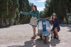 Zwei Frauen, die ein Auto auf Gasse aufheben Lizenzfreie Stockbilder