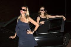 Zwei Frauen, die ein Auto bereitstehen Stockbild