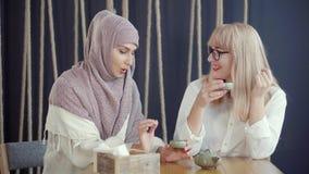 Zwei Frauen, die ein Gespräch in einem Café haben stock footage