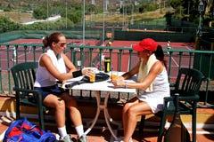 Zwei Frauen, die ein kaltes Getränk nach einem Spiel von Tennis in der Sonne genießen Stockfotos
