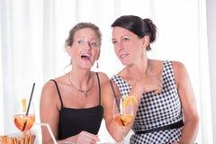 Zwei Frauen, die einen unsichtbaren Mann betrachten Stockfotos