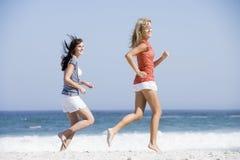 Zwei Frauen, die entlang Strand laufen Stockfotos