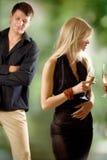 Zwei Frauen, die Gläser mit dem Schauen des Champagners und des jungen Mannes anhalten Stockbild