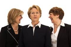 Zwei Frauen, die hinter der Rückseite des Chefs lachen Stockbild