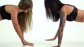 Zwei Frauen, die hoch fünf tun, drücken ups auf weißen Hintergrund stock video footage