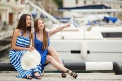Zwei Frauen, die im Hafen im Hintergrund aufwerfen, yachts Lizenzfreie Stockbilder