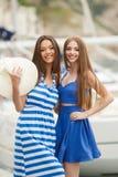 Zwei Frauen, die im Hafen im Hintergrund aufwerfen, yachts Stockfotos