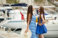 Zwei Frauen, die im Hafen im Hintergrund aufwerfen, yachts Lizenzfreie Stockfotos