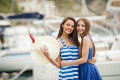 Zwei Frauen, die im Hafen im Hintergrund aufwerfen, yachts Stockbilder