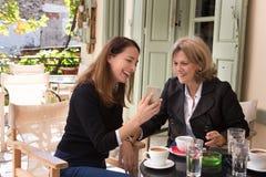Zwei Frauen, die Kaffee draußen trinken Lizenzfreies Stockfoto