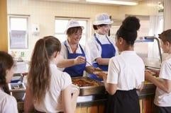 Zwei Frauen, die Kindern Lebensmittel in einer Schulcafeteria, hintere Ansicht dienen Lizenzfreie Stockfotos