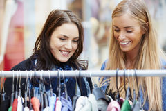 Zwei Frauen, die Kleidung auf Schiene im Einkaufszentrum betrachten Stockfotos