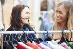 Zwei Frauen, die Kleidung auf Schiene im Einkaufszentrum betrachten Lizenzfreies Stockbild