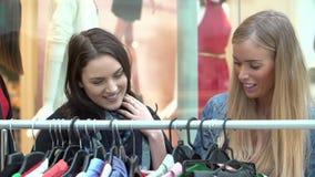 Zwei Frauen, die Kleidung auf Schiene im Einkaufszentrum betrachten stock video footage
