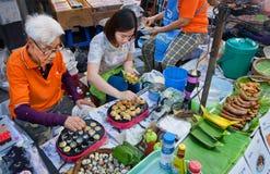 Zwei Frauen, die Lebensmittel von den Wachteleiern an der großen Straßenmesse mit schnellem Gastronomiebereich kochen Stockbilder
