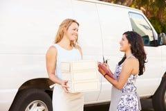 Zwei Frauen, die Lebensmittellieferanten mit Van laufen lassen lizenzfreie stockfotografie