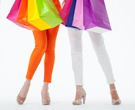 Zwei Frauen, die mehrfarbige Einkaufstaschen halten Stockfotos