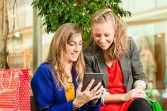 Zwei Frauen, die mit Beuteln im Mall kaufen Stockfoto