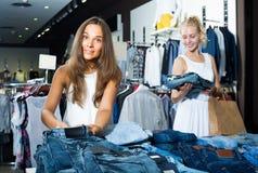 Zwei Frauen, die in Mode neue Abteilung der Jeans auswählen Lizenzfreie Stockbilder