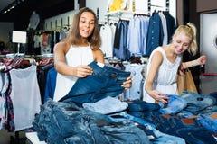 Zwei Frauen, die in Mode neue Abteilung der Jeans auswählen Stockfotografie