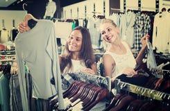 Zwei Frauen, die in Mode neuen Shop der Bluse auswählen lizenzfreies stockbild