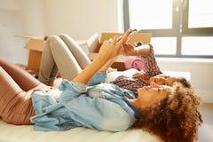 Zwei Frauen, die in neues Haus unter Verwendung Digital-Tablets umziehen Lizenzfreie Stockbilder