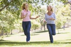 Zwei Frauen, die in Park und das Lächeln laufen Stockfotografie