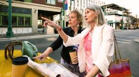 Zwei Frauen, die Richtungen in eine im Stadtzentrum gelegene Einstellung überprüfen lizenzfreie stockfotos
