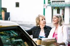 Zwei Frauen, die Richtungen mit einer Straßenkarte überprüfen stockbild