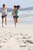 Zwei Frauen, die am Strand lachen und laufen Stockbild
