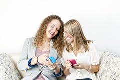 Zwei Frauen, die tragbare Geräte verwenden Stockfotos