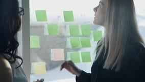 Zwei Frauen, die vor Schreibtisch im Büro stehen, besprechen Strategie stock video