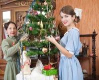 Zwei Frauen, die Weihnachtsbaum verzieren stockbilder