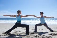 Zwei Frauen, die Yoga am Strand üben Stockbild