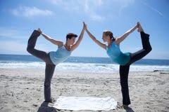 Zwei Frauen, die Yoga am Strand üben Stockbilder